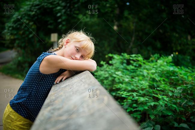 Girl leaning head on rural bridge
