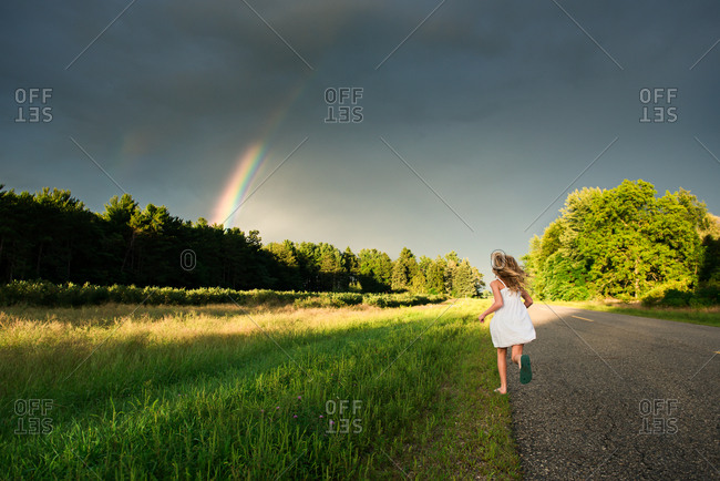Girl running to a rainbow