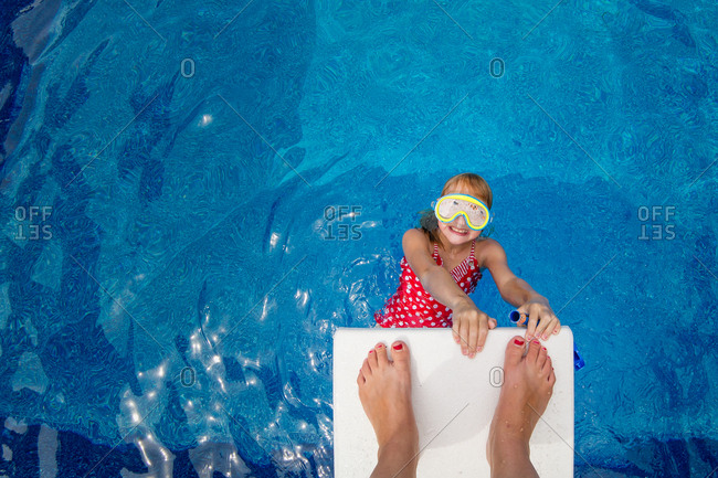 Girl hanging from a diving board