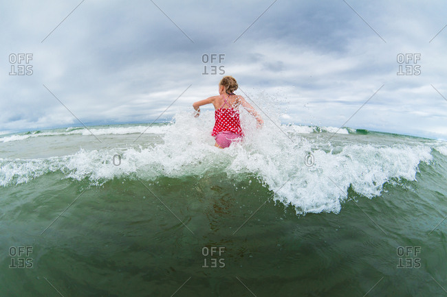 Girl running into a wave