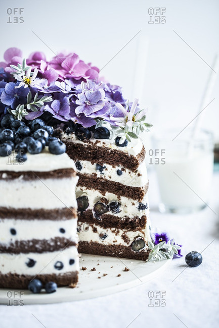 A cake with petals and blueberries
