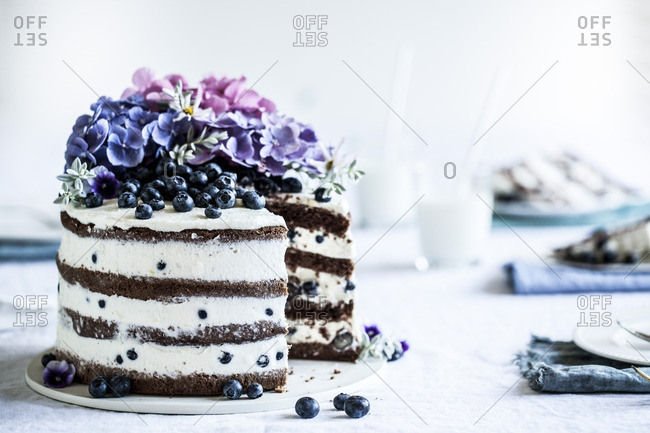 A cake with flowers and blueberries
