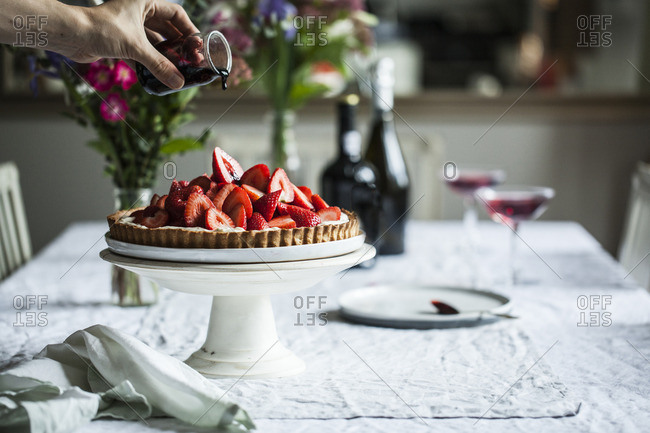 Pouring sauce over strawberry pie