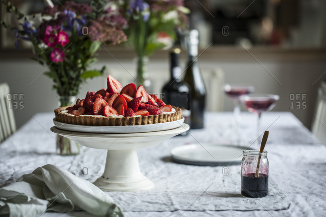 A strawberry topped pie on table