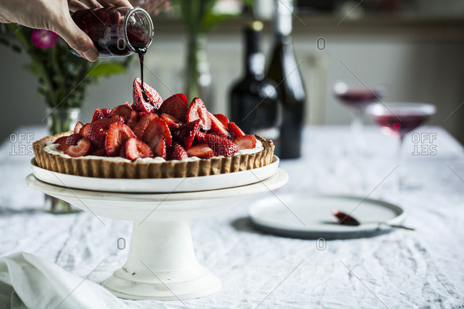 Pouring topping over strawberry cake