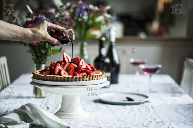 Pouring sauce over a strawberry pie