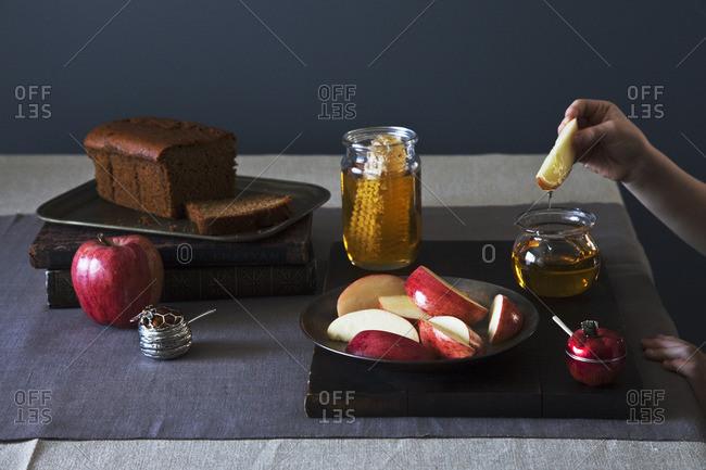 Dipping apple slice in honey