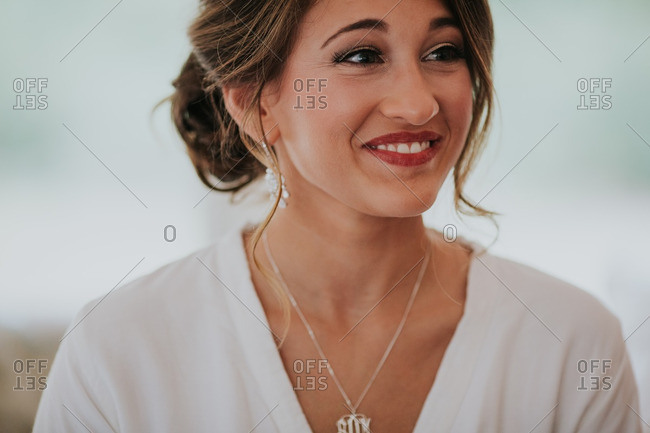 Close up of a bride in a white robe getting ready