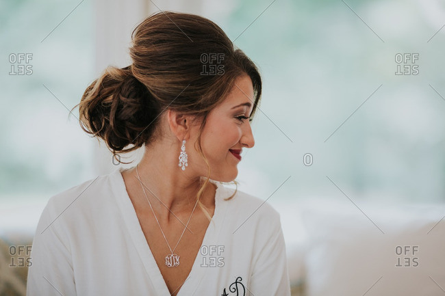 Happy bride wearing a white robe before her wedding