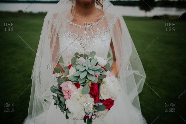 Mid-section of bride holding bouquet