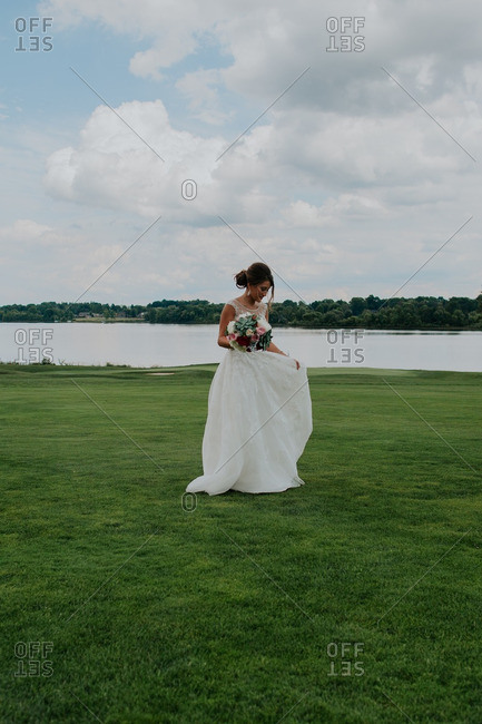 Bride walking on a golf course by a lake