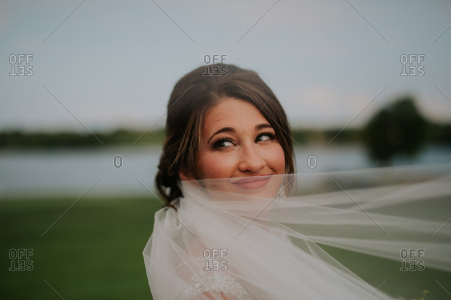 Portrait of a bride covering her mouth with her veil