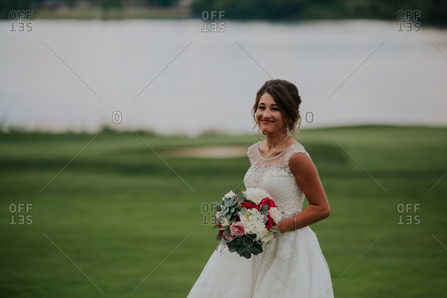 Bride standing on a golf course by a lake