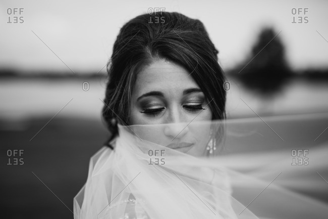 Black and white portrait of a bride covering part of her face with her veil