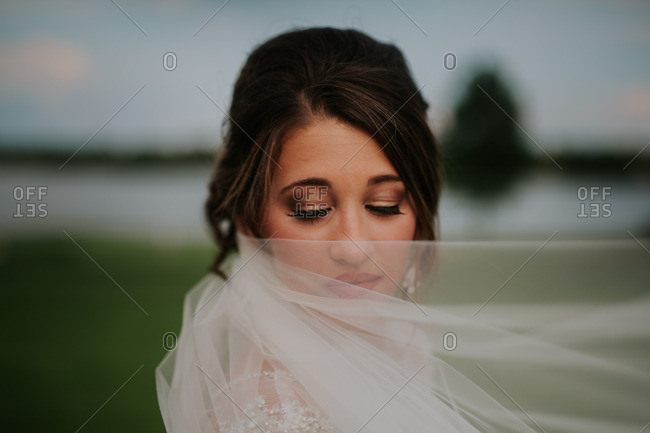Portrait of a bride covering part of her face with her veil