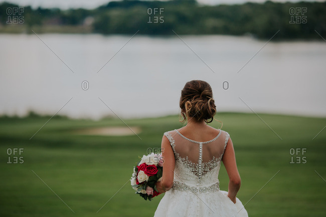 Bride looking out at a lake on a golf course