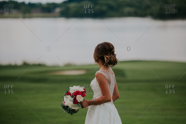 Bride walking by a lake on a golf course