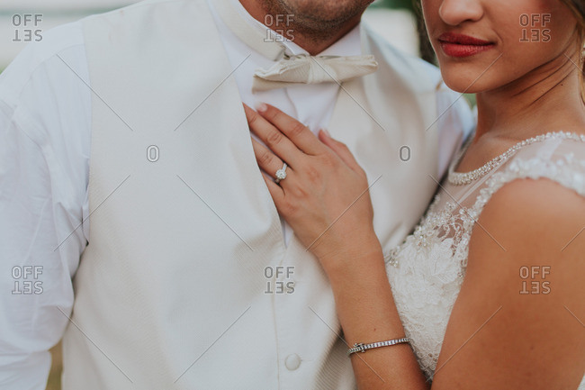 Close up of bride placing her hand on groom's chest
