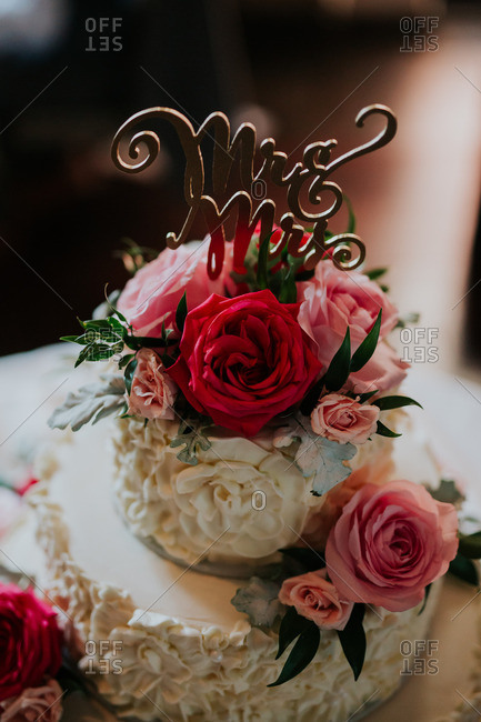 "Wedding cake with ""Mr. & Mrs."" topper and roses"