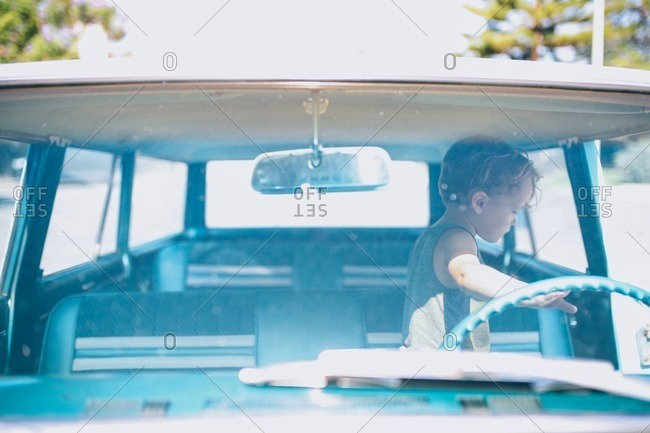 Little boy standing in front seat of old car