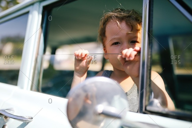 Little boy looking out window of old car