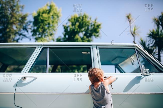 Little boy opening door of old car