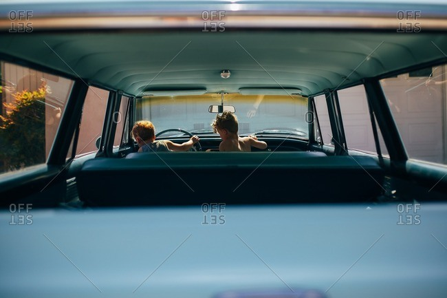 Two boys sitting in front seat of old car