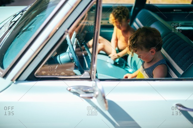 Two little boys sitting in front seat of old car