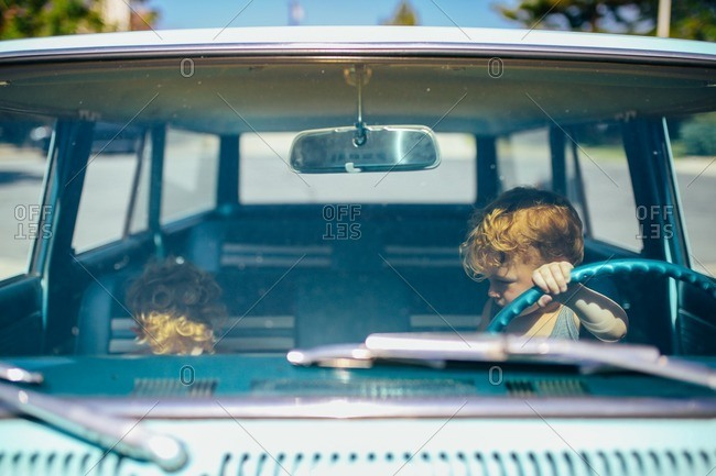 Two brothers sitting in front seat of old car