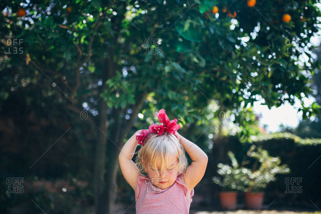 Little girl holding red flowers on her head