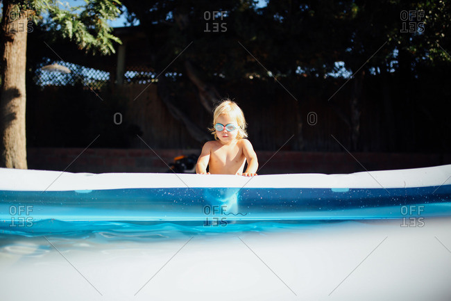 Little girl looking into a pool wearing goggles