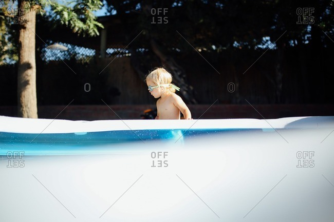 Little girl standing by an inflatable pool wearing goggles