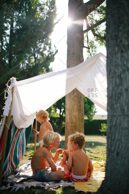 Siblings playing outside in a fort