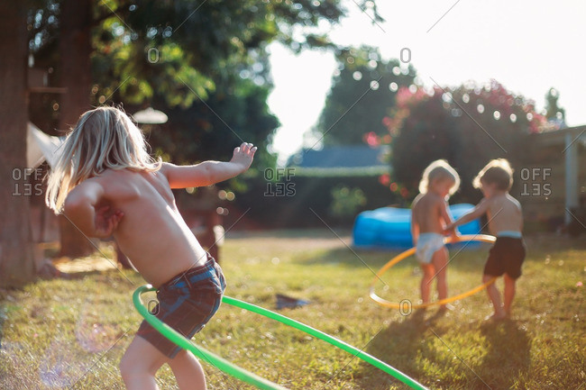 Siblings playing outside with hula hoops