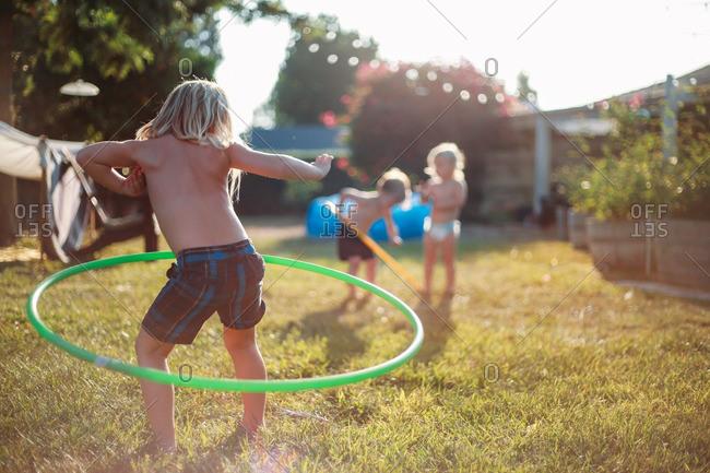 Children hula hooping in their backyard