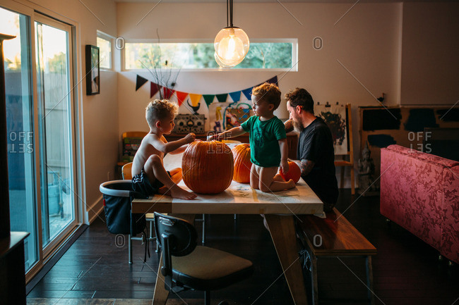 Father and his two sons carving pumpkins