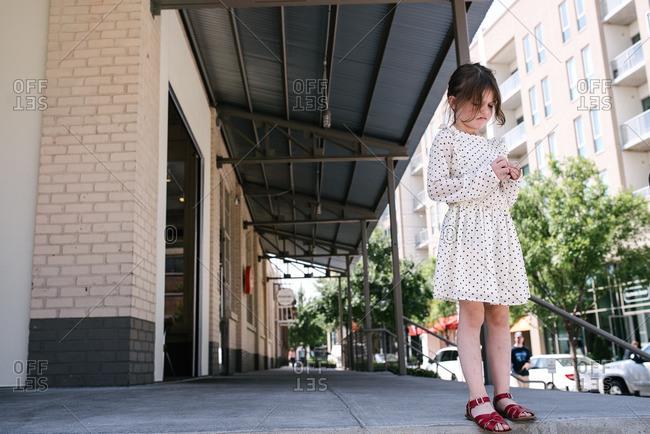 Girl standing alone on a city sidewalk