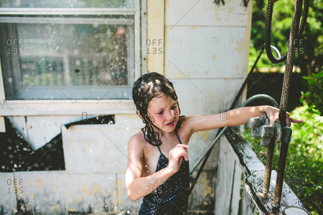 Girl trying to shut water off outdoors