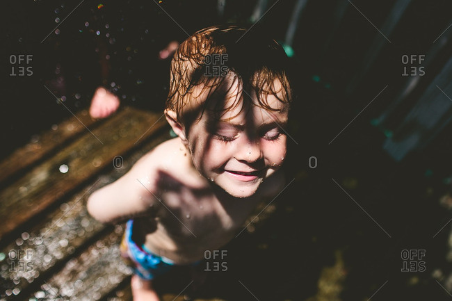Smiling boy being sprayed with water