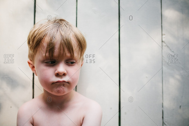 Portrait of a boy sitting in front of a white fence