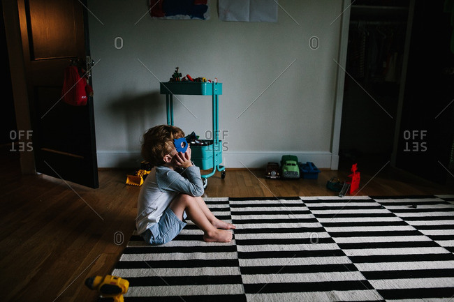 Boy sitting on floor wearing mask