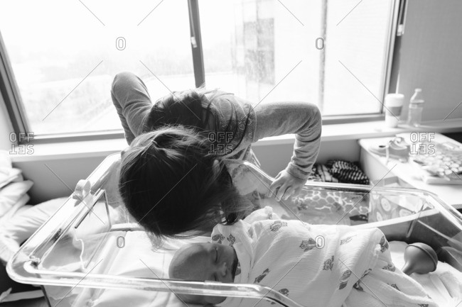 Little girl kissing her new baby brother in a hospital room