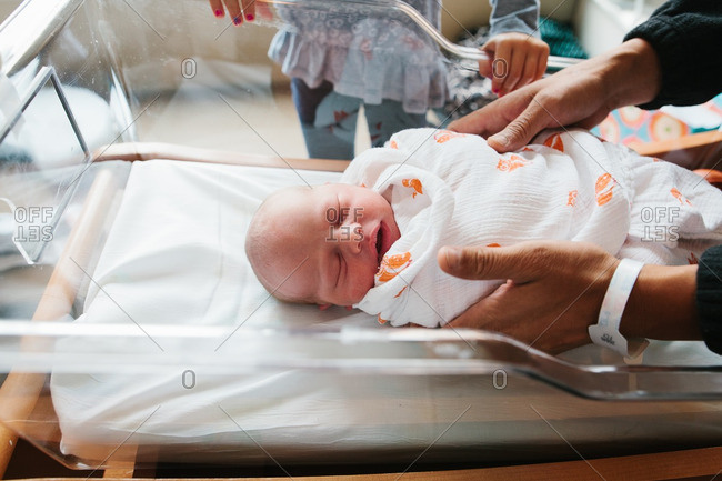 Father picking up new baby from hospital bed