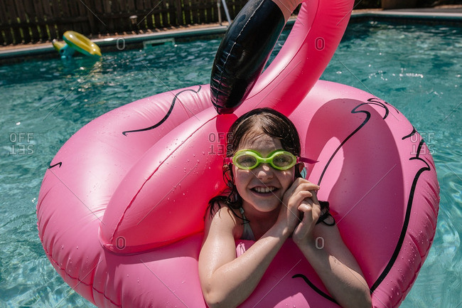 Girl floating in an inflatable pink flamingo in a pool