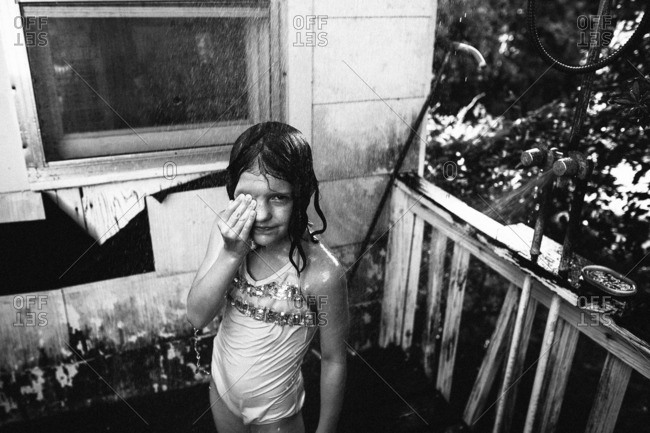 Girl being sprayed by water outdoors