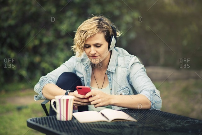 Woman listening to music while sitting at an outdoor table