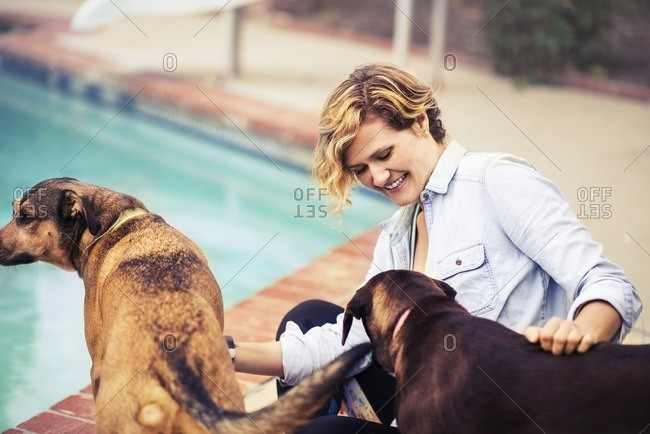 Woman sitting on ground petting her dogs poolside