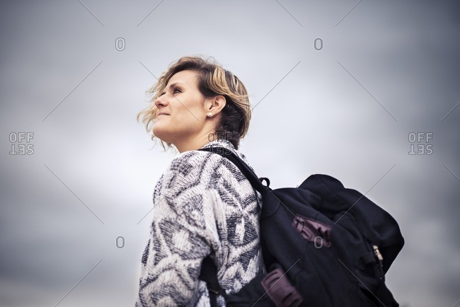 Low angle view of blonde woman backpacking