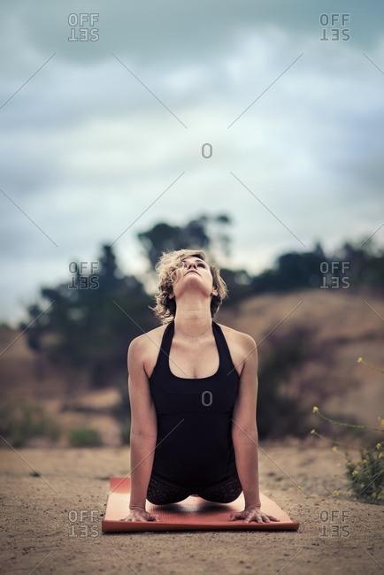 Woman doing cobra yoga pose outdoors