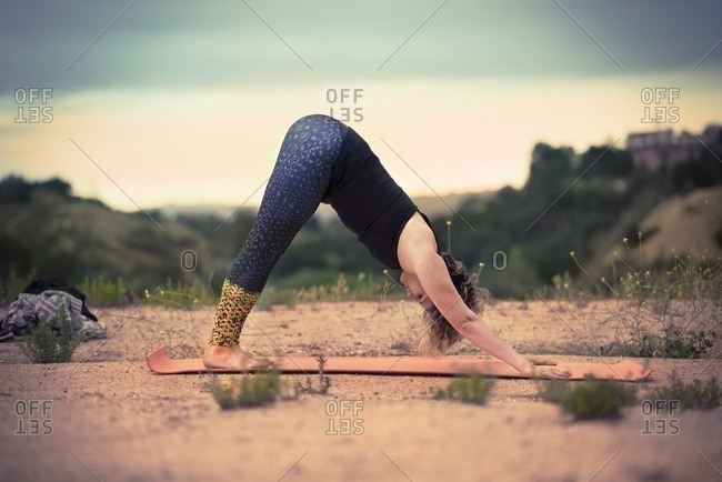 Woman doing the downward-facing dog yoga pose outdoors